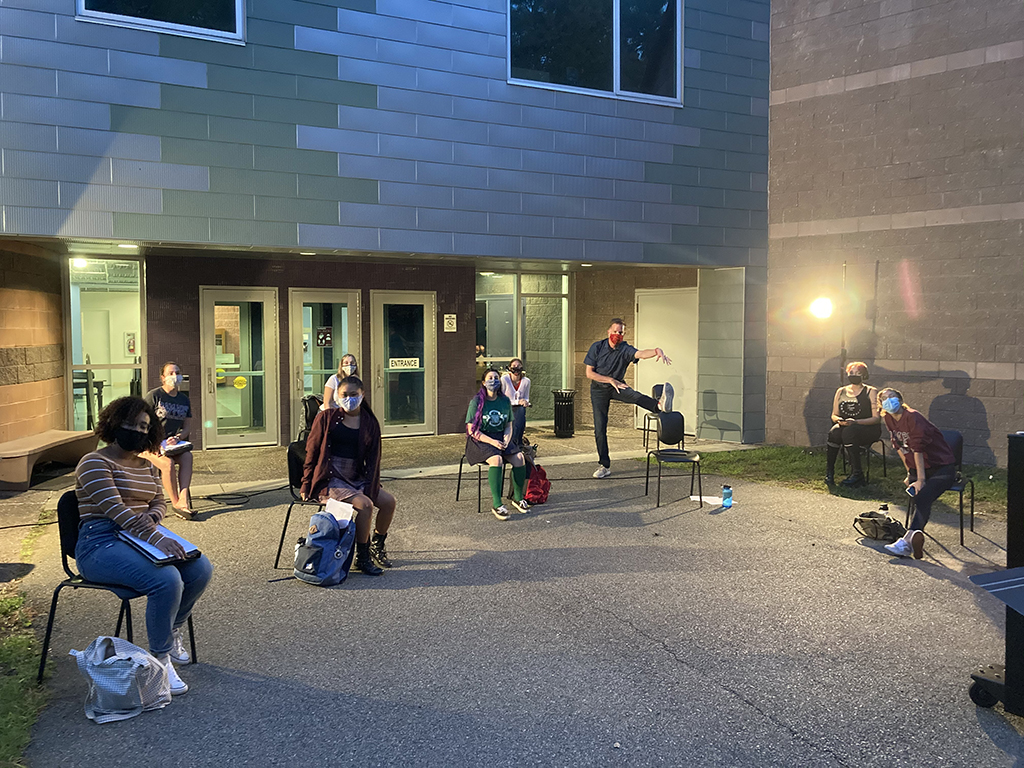 Students in CantaNOVA rehearsing outside the Berrie Center wearing masks and socially distancing