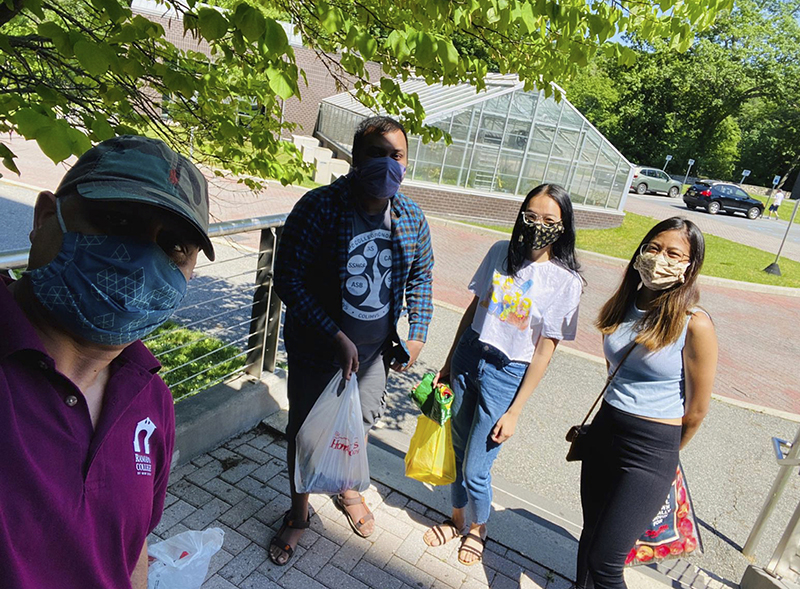 Rajesh Adhikari and three students wearing masks showing the food that was collected
