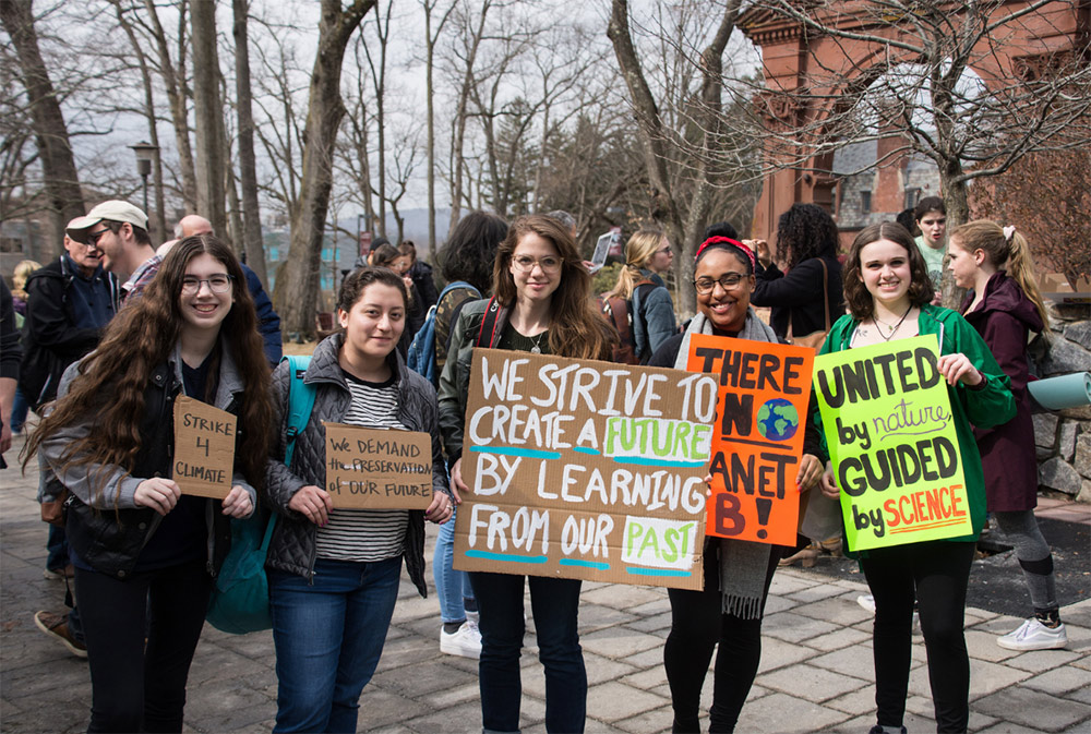 Students holding signs for a Climate Strike by the Ramapo College Arch